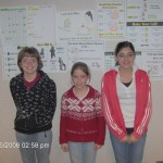 Our three students in front of training posters.