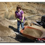 Katie filling the wheelbarrow with dirt.